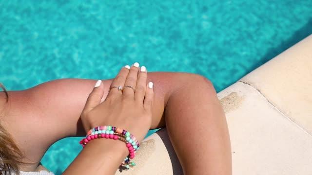 kvinna som applicerar sollotion på armen med vid poolen en varm, solig dag. - brunbränd bildbanksvideor och videomaterial från bakom kulisserna