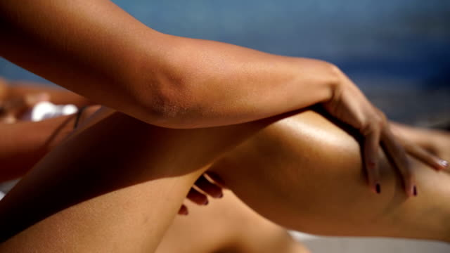 Woman applying sun lotion on her leg with a spray at the beach on a hot, sunny day. Skin care, sunblock protection concept video
