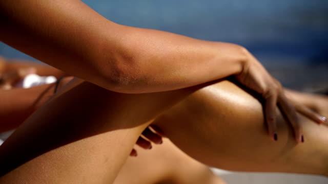 vídeos de stock e filmes b-roll de woman applying sun lotion on her leg with a spray at the beach on a hot, sunny day. skin care, sunblock protection concept - protetor solar