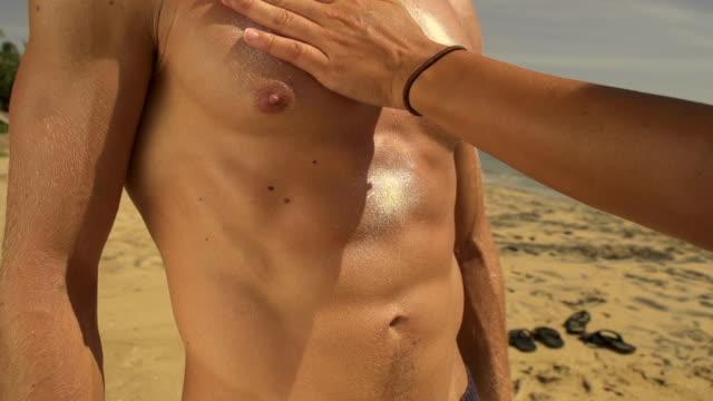Woman applying sunblock on muscular man video