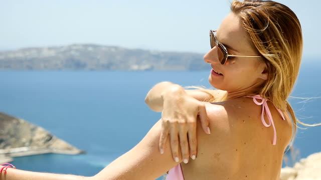 Woman applying suntan lotion video