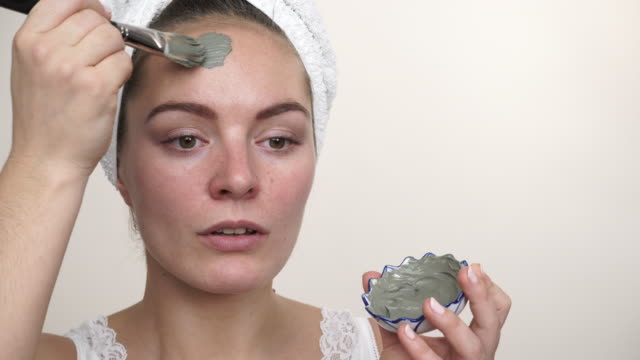woman applying with brush clay mud mask to her face 4k - viziarsi video stock e b–roll