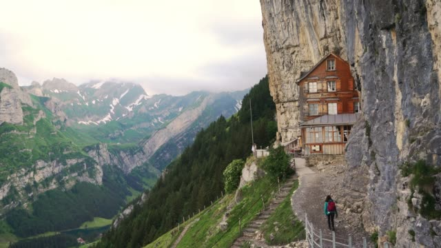 woman approaching to wooden hut in appenzell - capanna video stock e b–roll