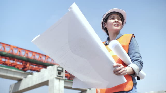 woman architect discussing on blueprint at construction site - direttrice video stock e b–roll