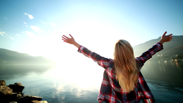 Woman arms outstretched by the lake video