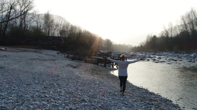 Woman arms outstretched by the river video