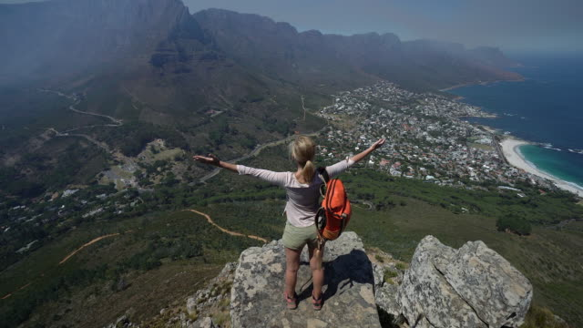 Woman arms outstretched on top of Lion's head Woman arms outstretched on top of Lion's head, Cape Town table mountain national park stock videos & royalty-free footage