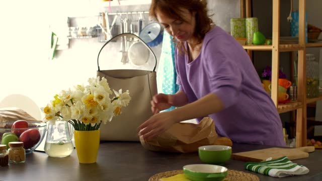 Woman arranging flowers and unloading groceries in the kitchen