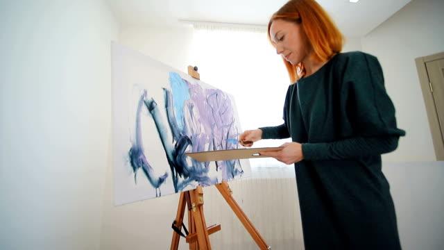 vidéos et rushes de artiste femme commence à peindre une image avec une spatule et des peintures acryliques. création d'un dessin sur la toile - toile à peindre