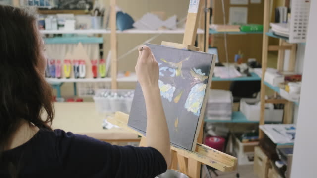 Woman artist is making strokes by paints in workshop, drawing a picture