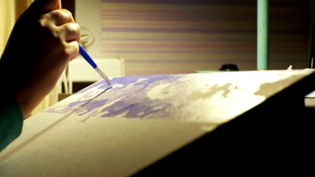 woman artist sitting at a table draws a picture at home - tavolozza video stock e b–roll