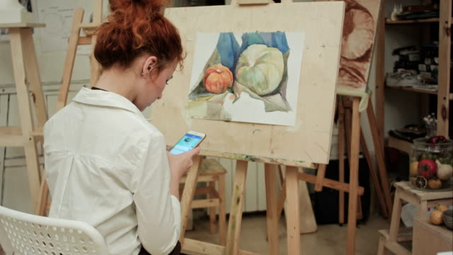 Woman artist sitting in front of easel messaging on the phone video