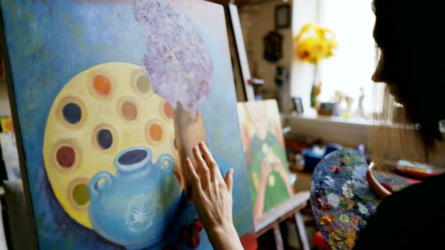 Woman artist smearing oil paints on canvas picture in art workshop video