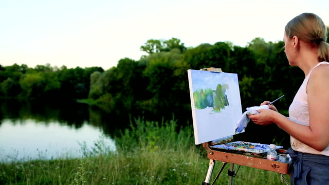 A woman artist with a brush and polytray in her hands draws on canvas against the backdrop of nature. The artist draws on the easel. Artist at work video