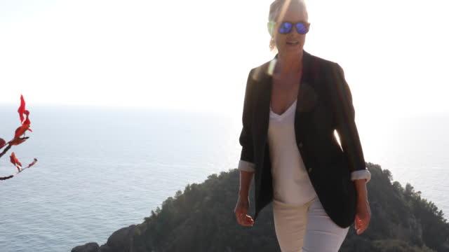 vídeos de stock e filmes b-roll de woman ascends slope to look out to sea view - 55 59 anos