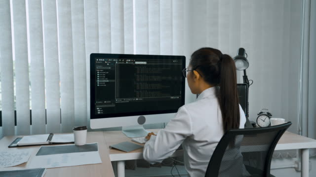 Woman asian software developers are analyzing about the code written into the program on the computer in office room.