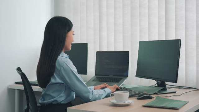 Woman asian software developers are analyzing together about the code written into the program on the computer in office room.