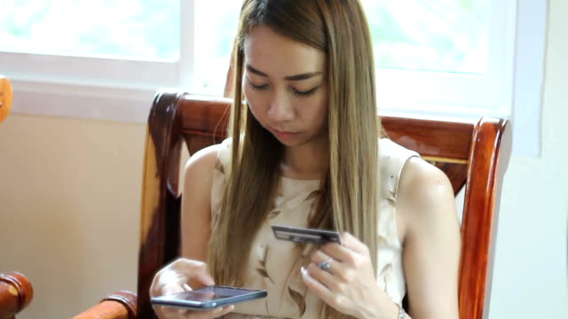 woman asian using phone and credit card shopping online video