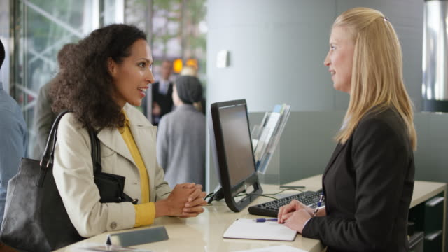 Woman asking the rental agent for a rental car type and the female agent searches in her computer Wide handheld shot of a woman at the counter in a car rental office asks the agent for a rental car and she looks it up in her computer. Shot in Slovenia. car rental stock videos & royalty-free footage