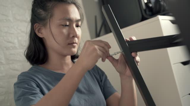Woman assembling furniture video