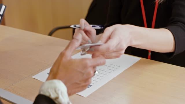 vídeos de stock, filmes e b-roll de mulher, ajudando os participantes da conferência com o check-in no balcão - distintivo