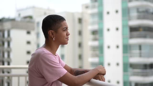 Woman at apartment's porch looking at view