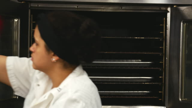 Woman at bakery placing trays of cookies in an oven to bake video