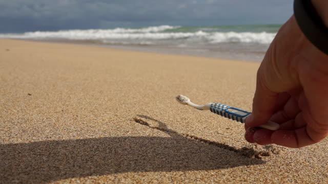 Frau am Strand entfernen Kunststoff Verschmutzung Zahnbürste Umweltreinigung – Video