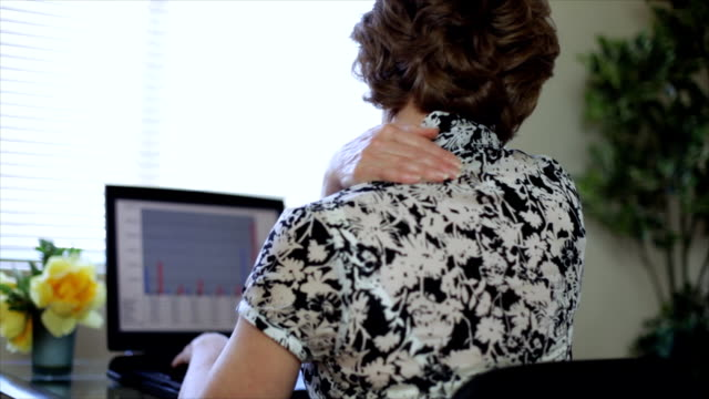 stockvideo's en b-roll-footage met woman at computer has neck and shoulder pain - nek