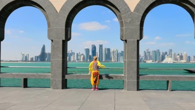vidéos et rushes de woman à doha skyline - doha
