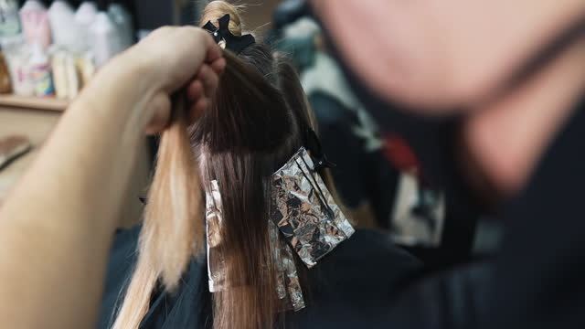Woman at hair salon Hairdresser is dyeing female hair, making hair highlights to his client with a foil. They are wearing protective face mask as protection against virus pandemic. highlights hair stock videos & royalty-free footage