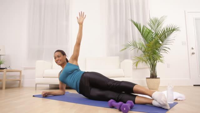 woman at home doing yoga - black woman towel workout bildbanksvideor och videomaterial från bakom kulisserna
