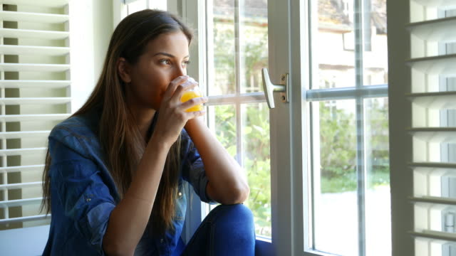 Woman at home looking through the window video