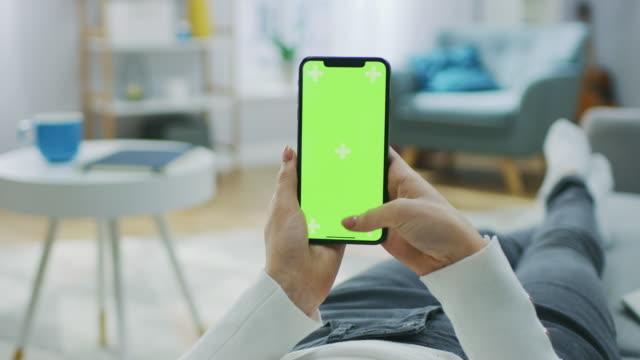 kvinna på hem ligger på en soffa med smartphone med grön mock-up skärm, gör svepa, rullning gester. flicka med mobiltelefon, internet sociala nätverk surfar. synvinkel kamera skott. - skrollning bildbanksvideor och videomaterial från bakom kulisserna