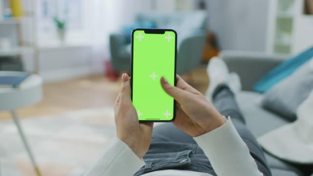ホーム グリーン モックアップ画面、スワイプしてスクロール ジェスチャーでスマート フォンを使用してソファに横になっている女性。携帯電話のブラウジング インターネットの社会的ネ� - ソファ 女性点の映像素材/bロール