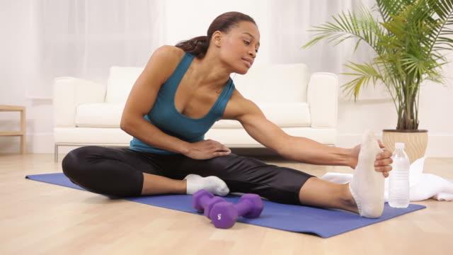 woman at home stretching and exercising - black woman towel workout bildbanksvideor och videomaterial från bakom kulisserna