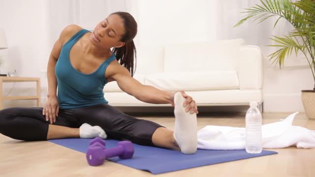 woman at home stretching before workout - black woman towel workout bildbanksvideor och videomaterial från bakom kulisserna