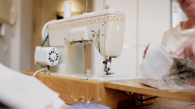 donna a casa con una macchina da cucire. - sarta video stock e b–roll
