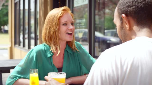 kobieta na zewnątrz kawiarni rozmawia z jej data, ponieważ napoje jego mimoza - scone filmów i materiałów b-roll