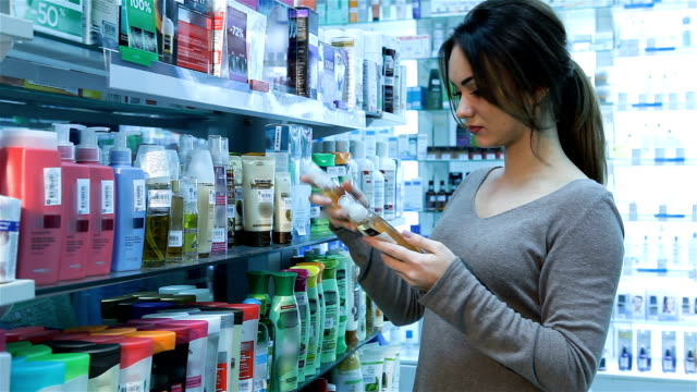 Woman at pharmacy buying shampoo video