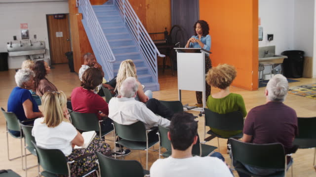 コミュニティセンターでの表彰台議長近隣会議の女性 - community activism点の映像素材/bロール