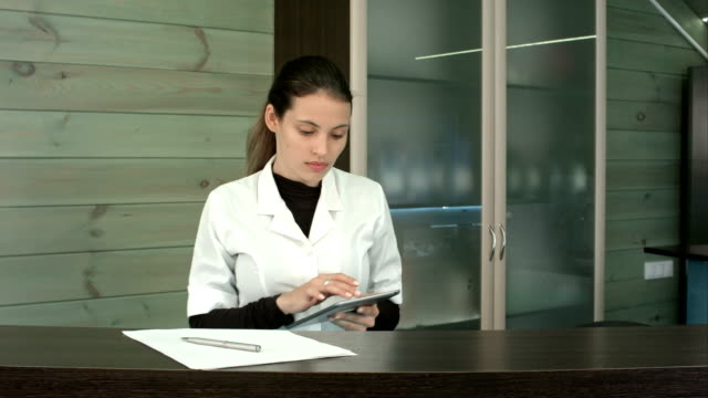 Vrouw op spa receptie gebruikt tablet pc texting aan client video