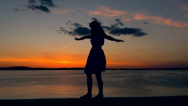 woman at sunset walking along the waterfront raising her hands to the side - equilibrio video stock e b–roll