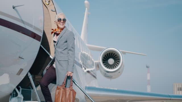 Woman at the airport Senior woman entering the private jet airplane at the airport and waving to someone. wealth stock videos & royalty-free footage
