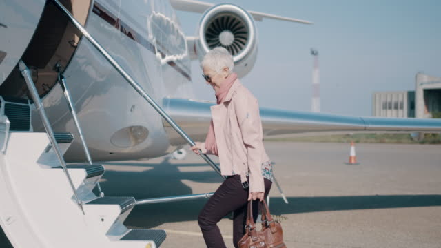 Woman at the airport Senior woman entering the private jet airplane at the airport and waving to someone. private airplane stock videos & royalty-free footage