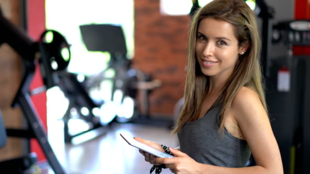 Woman at the gym browsing on her tablet
