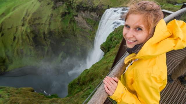 donna in cima alla cascata islandese skogafoss sorridente nella telecamera - spettinato video stock e b–roll