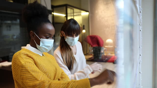Woman at work in the office wearing protective face covering mask video