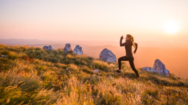 Woman athlete running uphill at sunset Woman athlete running uphill over rocky trails and grassy slopes at sunset life balance stock videos & royalty-free footage