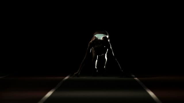 vidéos et rushes de femme athlète s'étend vers la caméra - starting block